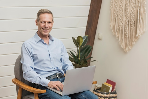 Moderner älterer mann, der einen laptop anhält Kostenlose Fotos
