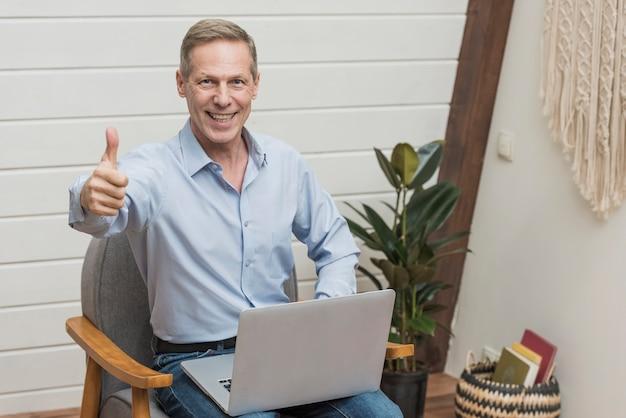 Moderner älterer mann der vorderansicht, der einen laptop hält Kostenlose Fotos