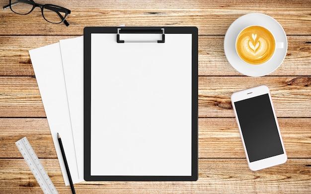Moderner arbeitsplatz mit kaffeetasse, papier, notizbuch, tablette oder smartphone und klemmbrett auf holz Premium Fotos