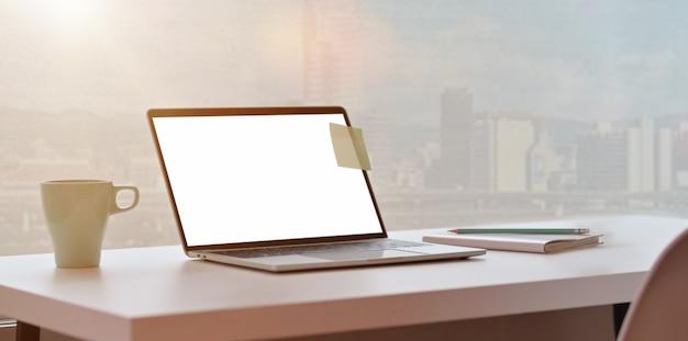Moderner arbeitsplatz mit laptop- und stadtansichthintergrund Premium Fotos
