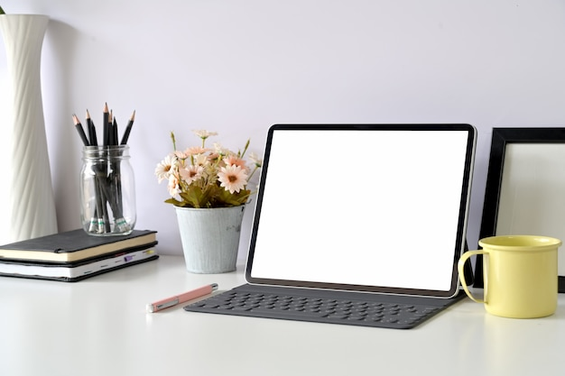 Moderner arbeitsplatz mit tablette des leeren bildschirms des modells Premium Fotos