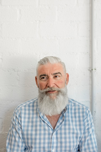 Moderner bärtiger älterer mann im hemd im salon Kostenlose Fotos