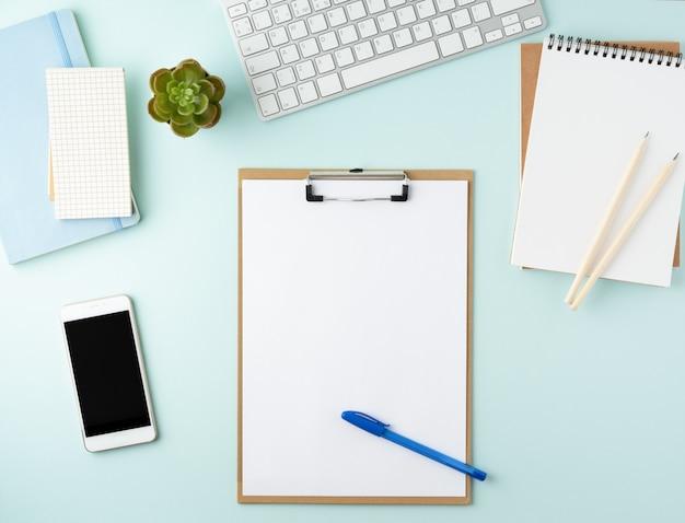 Moderner blauer bürodesktop der draufsicht mit leerem notizblock Premium Fotos