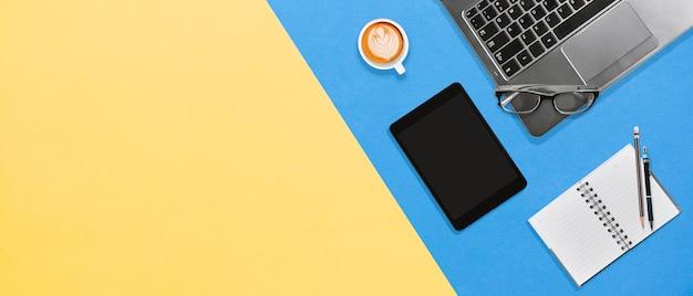 Moderner bürodesktoparbeitsplatz mit laptop, notizbuch, tablette, heißer kaffee mit kopienraum Premium Fotos