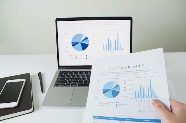 Moderner bürofokus auf dem laptopschirm mit diagrammen und diagrammen. mit papier, diagrammen und diagrammen in den händen von geschäftsleuten. Premium Fotos