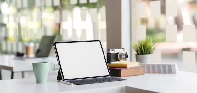 Moderner büroraum mit tablette, kamera und büroartikel des leeren bildschirms Premium Fotos