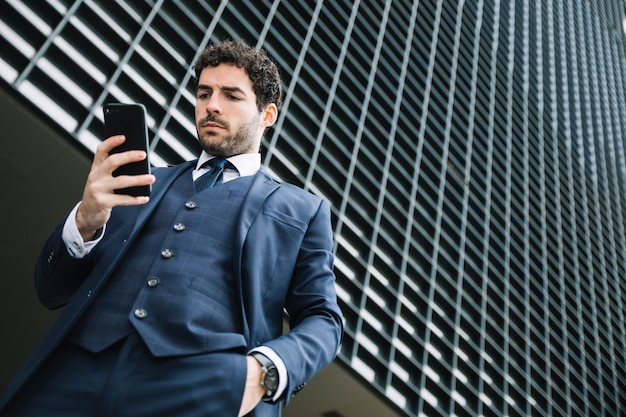 Moderner geschäftsmann unter verwendung des smartphone draußen Kostenlose Fotos
