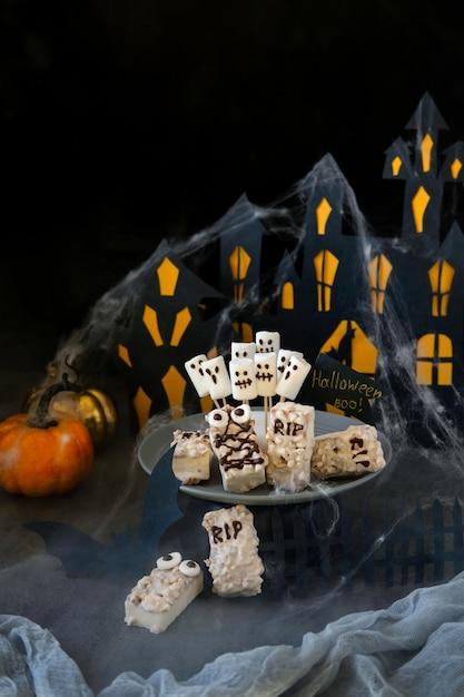 Moderner halloween-hintergrund. halloween schokoriegel: lustige monster aus keksen mit schokolade und geister marshmelow nahaufnahme auf dem tisch Premium Fotos