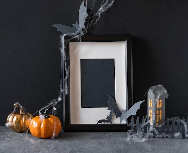 Moderner halloween-hintergrund mit kürbissen, fledermäusen und schwarzem rahmen auf dunklem hintergrund Premium Fotos