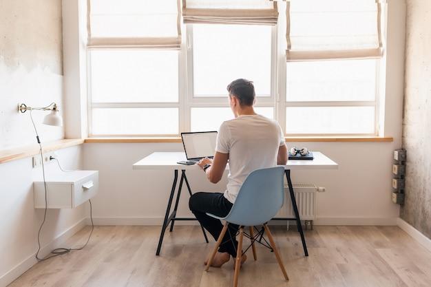 Moderner junger gutaussehender mann im lässigen outfit, das am tisch sitzt am laptop, freiberufler zu hause Kostenlose Fotos