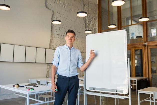 Moderner junger hübscher lächelnder mann, der an leerer weißer tafel mit markierung steht, Kostenlose Fotos
