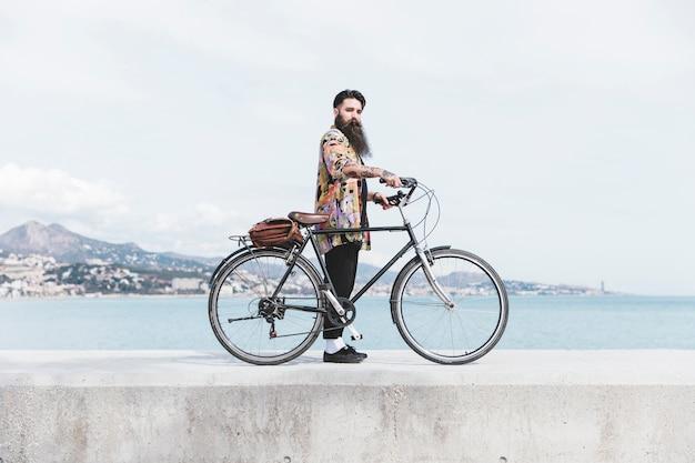 Moderner junger mann mit seinem fahrrad, das auf wellenbrecher nahe der küste steht Kostenlose Fotos