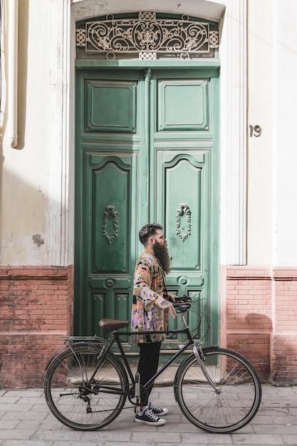 Moderner junger mann mit seinem fahrrad, das vor grüner tür steht Kostenlose Fotos