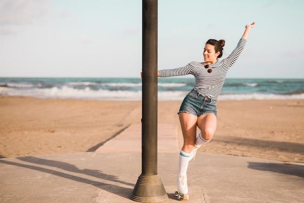 Moderner junger weiblicher schlittschuhläufer, der säulentanzen am strand hält Kostenlose Fotos