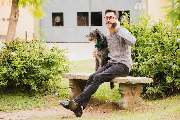 Moderner mann, der im park mit seinem hund spricht am handy sitzt Kostenlose Fotos