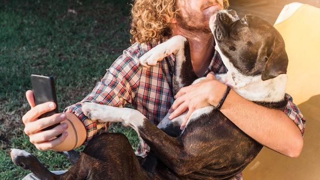 Moderner mann mit hund im garten Kostenlose Fotos