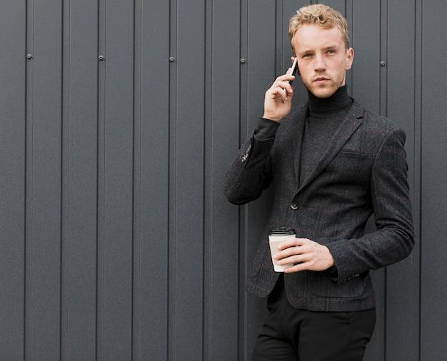 Moderner mann mit kaffee sprechend am telefon Kostenlose Fotos