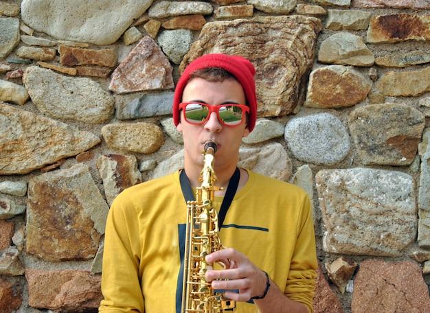 Moderner musiker, der mit seinem saxophon im garten aufwirft Premium Fotos