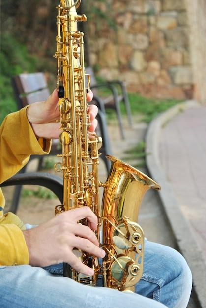 Moderner musiker, der mit seinem saxophon im strand aufwirft Premium Fotos