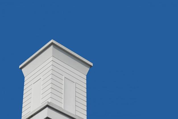 Moderner retro- weißer hölzerner kamin mit hintergrund des blauen himmels. Premium Fotos
