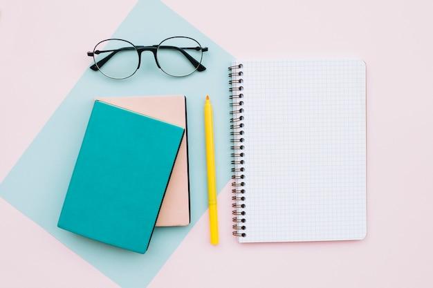 Moderner schreibtisch mit gläsern und büchern und notizbuch auf pastellfarbhintergrund Kostenlose Fotos