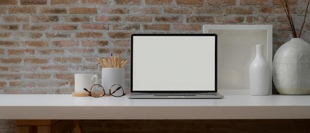 Moderner schreibtisch mit laptop mit weißem bildschirm Premium Fotos