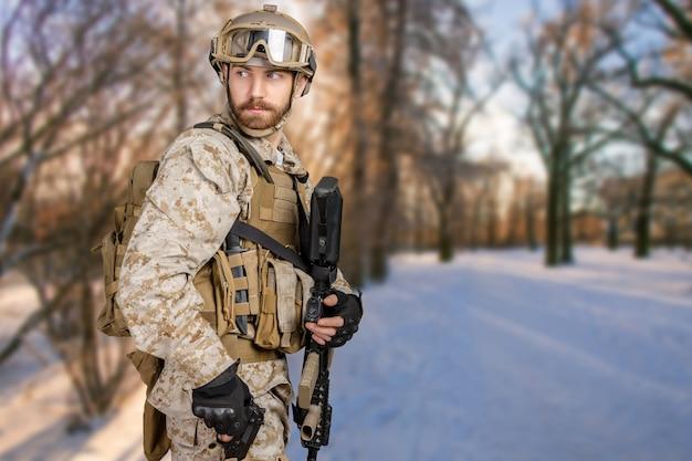 Moderner soldat mit gewehr in einem wald Premium Fotos