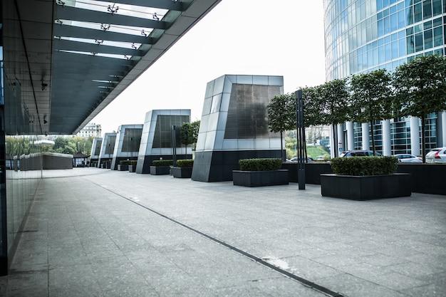 Moderner stadtstraßenfußweg mit glasfensterwand und -sonnenlicht Premium Fotos