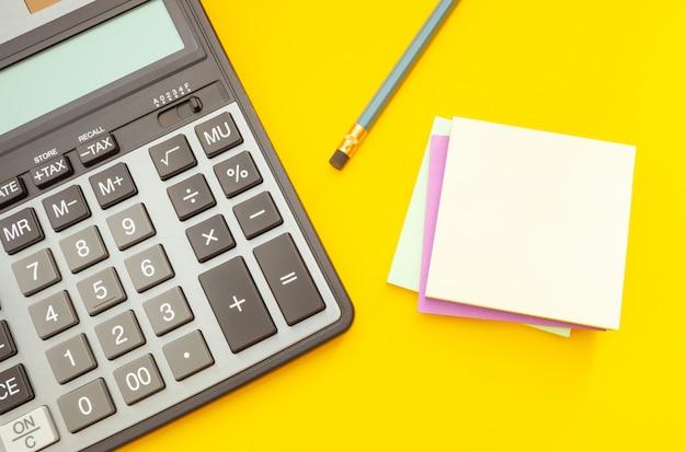 Moderner taschenrechner und bleistift mit aufklebern für anmerkungen Premium Fotos