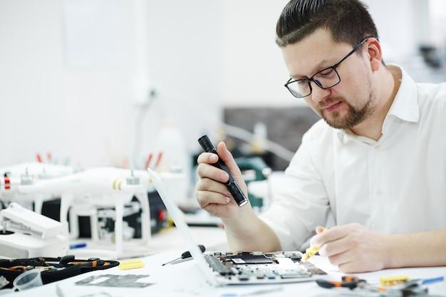 Moderner techniker inspecting laptop mit taschenlampe Kostenlose Fotos