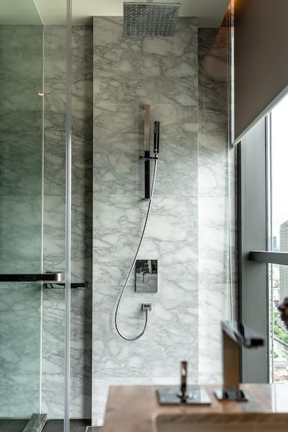 Modernes badezimmer mit duschgarnitur aus edelstahl und weißer naturmarmorwand / innenarchitektur / kopierraum Premium Fotos