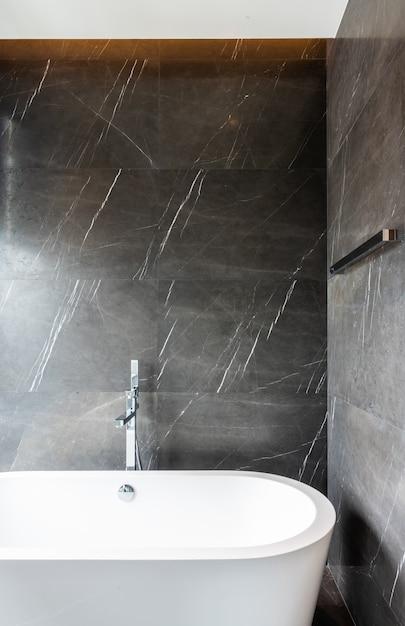 Modernes badezimmerinterieur mit badewanne und brauner naturmarmorwand / innenarchitektur / kopierraum Premium Fotos