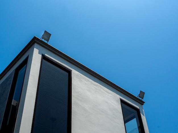 Modernes betongebäude mit led-flutlicht oben auf blauem himmel Premium Fotos