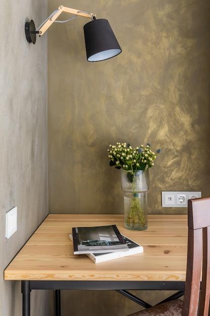 Modernes büro. ein schreibtisch und ein stuhl daneben. die wand ist mit grünem dekorputz bedeckt, eine vase mit blumen und zeitschriften auf dem tisch Premium Fotos