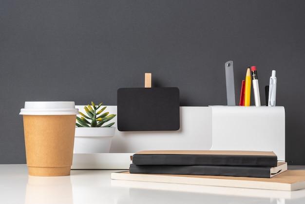Modernes bürobriefpapier auf weißer tabelle und dunkelgrauer wand Premium Fotos