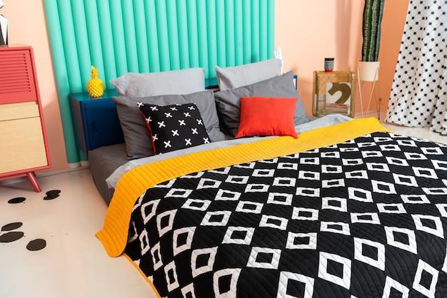 Modernes buntes hipster ungewöhnliches schlafzimmer mit schwarzweiss-textil und hellen akzenten. Premium Fotos