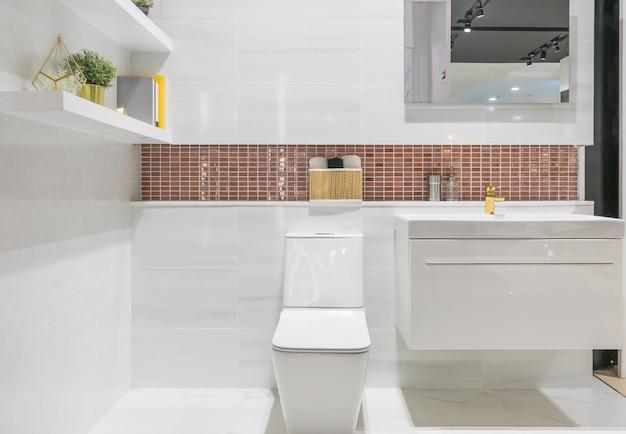 Modernes geräumiges badezimmer mit hellen fliesen mit wc und waschbecken. Premium Fotos