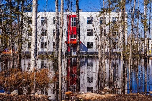 Modernes haus und eine große pfütze in der nähe, überfluteter bereich Premium Fotos