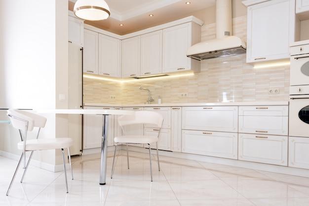 Modernes, helles, sauberes kücheninterieur in einem luxushaus. innenarchitektur mit klassischen oder vintage-elementen. praktische und gut eingerichtete küche. Premium Fotos