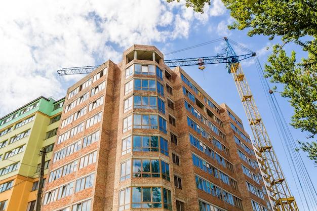 Modernes hochhausgebäude im bau mit turmkran und grünem baum Premium Fotos