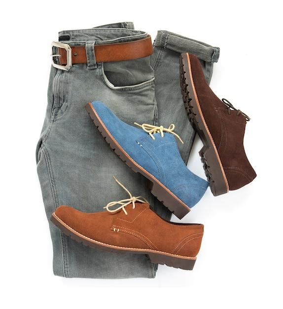 Modernes konzept, mannkleidung stellte mit unterschiedlicher farbe von den schuhen, von grauen jeans und von gürtelleder ein, die auf weißem hintergrund lokalisiert wurden. ansicht von oben Premium Fotos