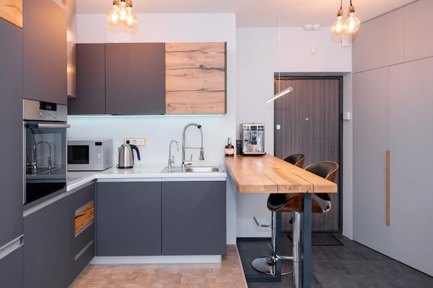 Modernes kücheninterieur mit lichtern auf braunem holztisch und barhockern, kaffeemaschine. zeitgemäßes interieur mit loft-elementen Premium Fotos