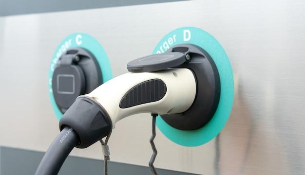 Modernes ladegerät für elektroautos in ev-ladestation, umweltfreundliche kraftstoffversorgung oder hybridfahrzeugtechnologie Premium Fotos