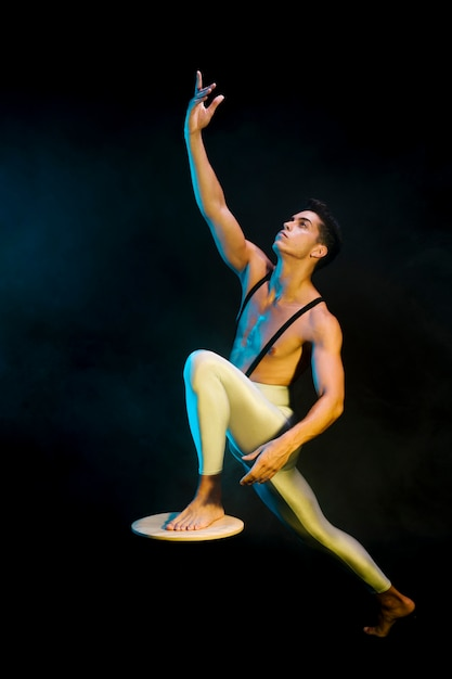 Modernes männliches ballettausführertanzen im scheinwerferlicht Kostenlose Fotos