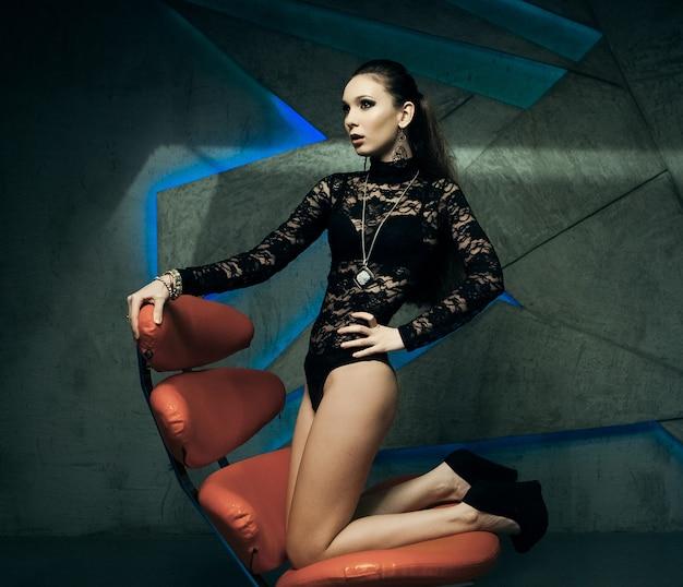 Modernes modell, das in einem roten stuhl sitzt Premium Fotos
