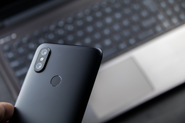 Modernes notebook und smartphone. mobil mit doppelkamera und fingerabdruckleser Premium Fotos