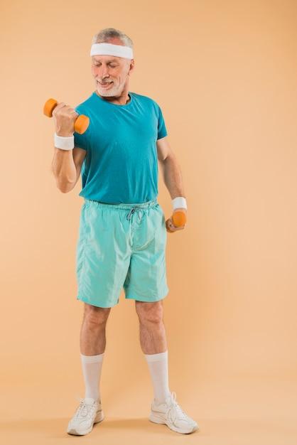 Modernes training des älteren mannes mit dummköpfen Kostenlose Fotos