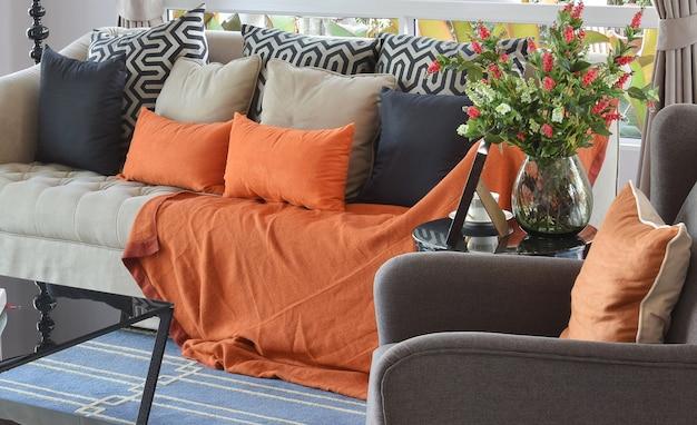Modernes wohnzimmerdesign mit braunem und orangefarbenem tweedsofa und schwarzen kissen Premium Fotos