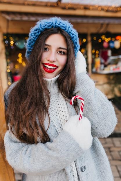 Modische brünette frau in den weißen handschuhen, die winterzeit genießen. außenporträt des raffinierten langhaarigen weiblichen modells im stilvollen blauen hut, der mit vergnügen am kalten morgen aufwirft, der weihnachtssüßigkeit hält. Kostenlose Fotos