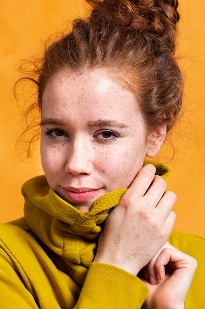 Modische frau der nahaufnahme, die mit gelbem hoodie aufwirft Kostenlose Fotos